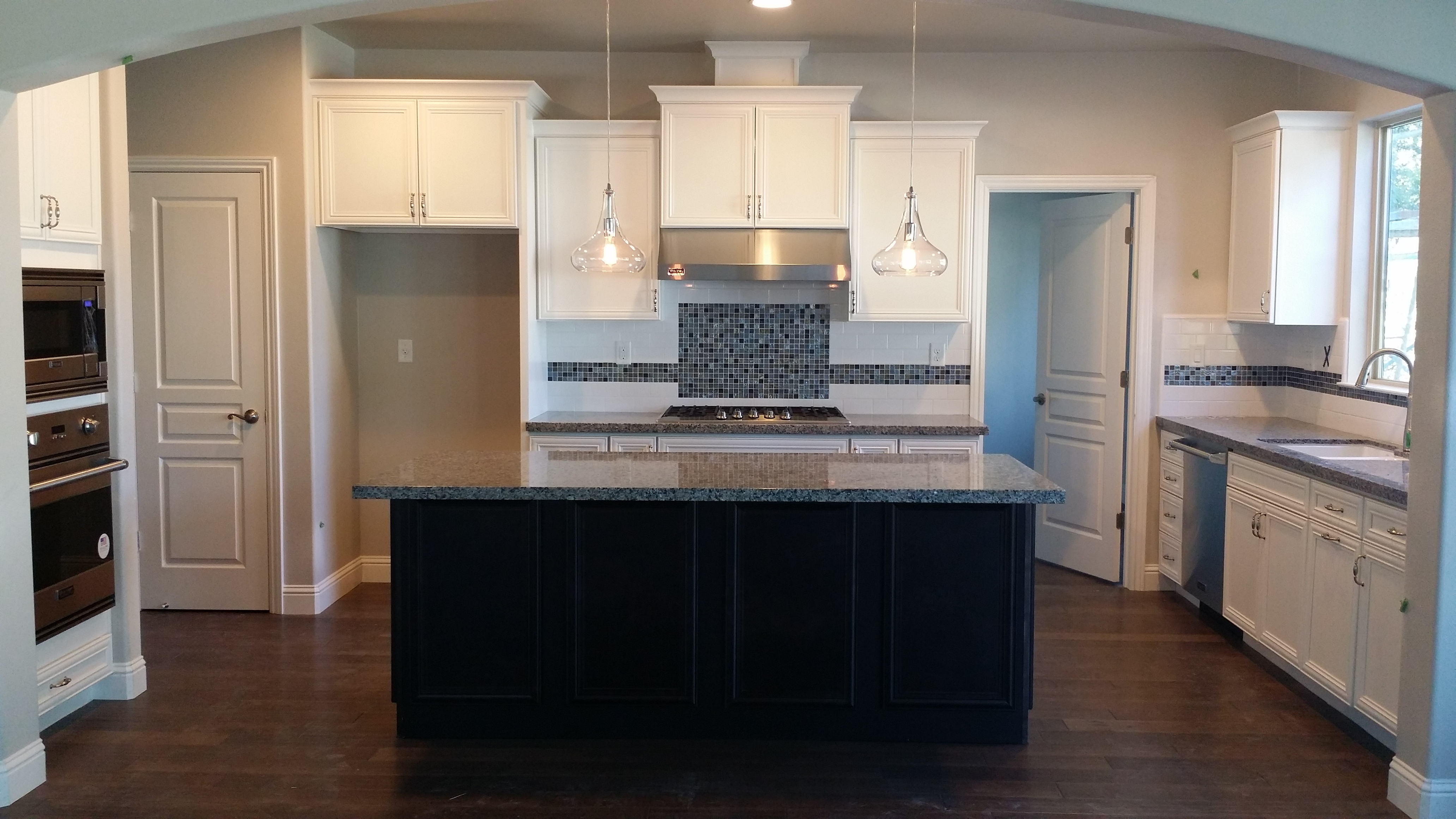 Traditional kitchen with white cabinets, a black island, and black counters
