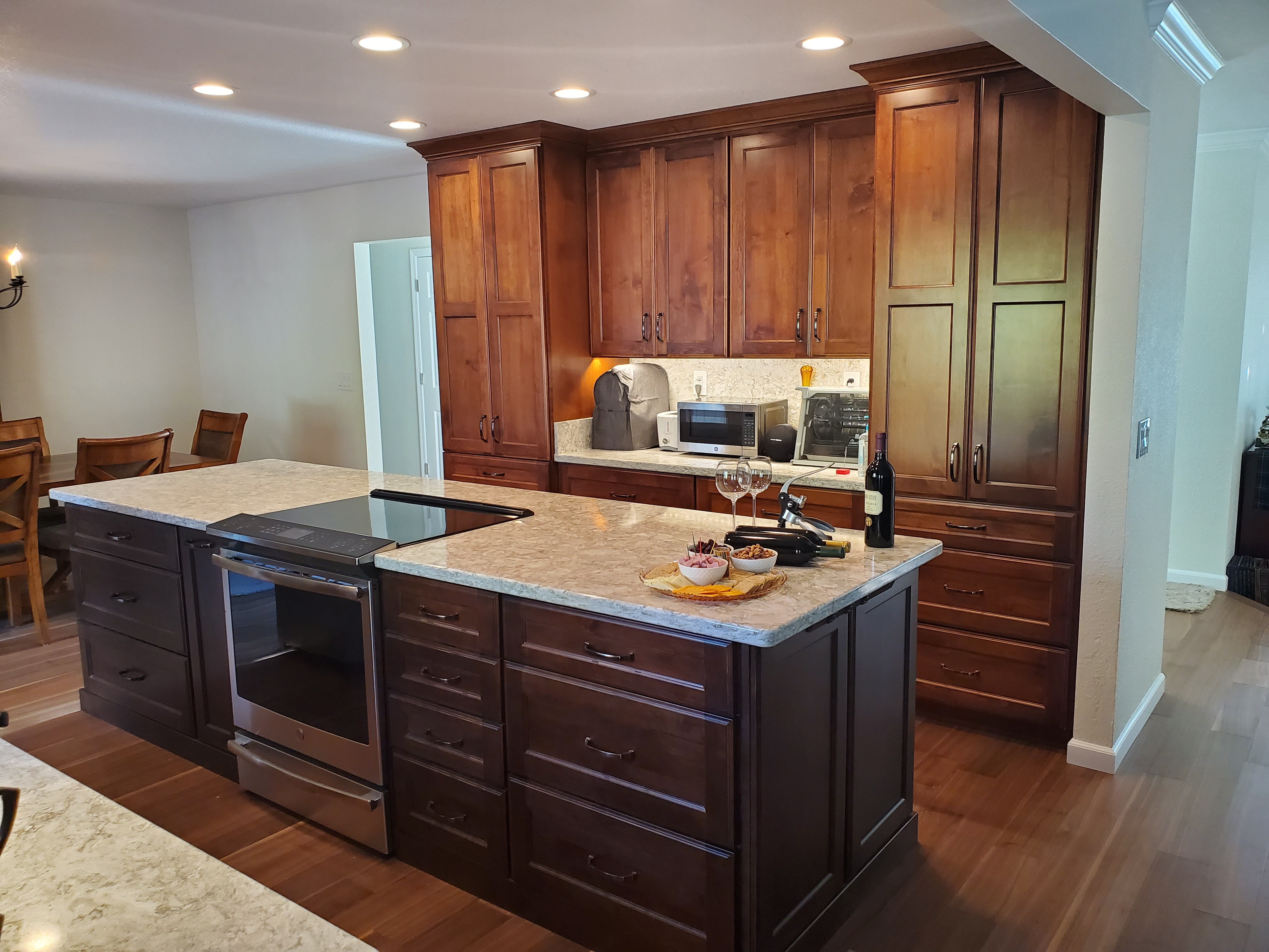 Kitchen island with oven, white counters, cabinets.