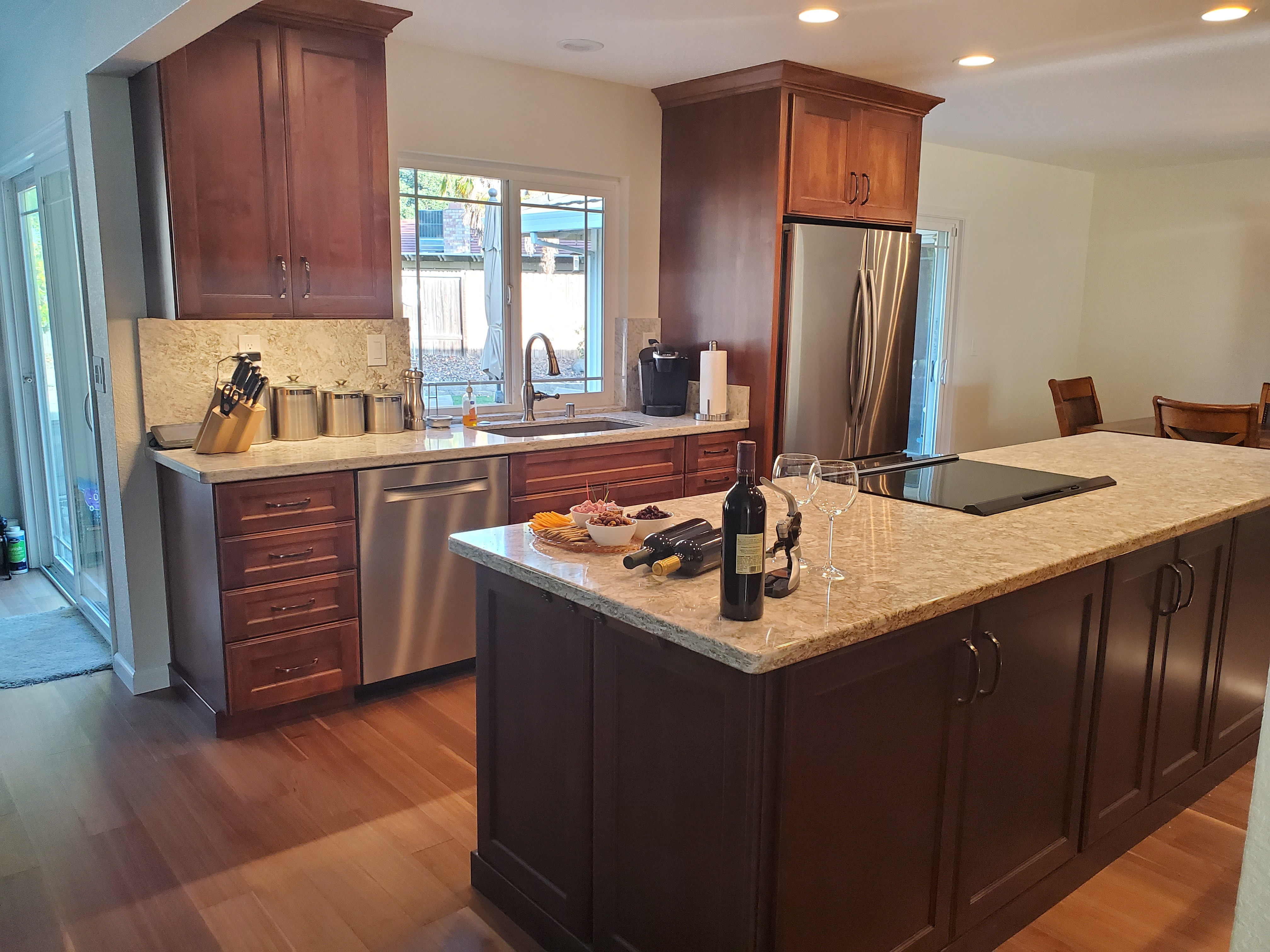 Traditional kitchen with island, stainless appliances, white counters and dark wood cabinets