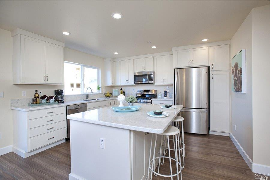 All white kitchen with stainless appliances.