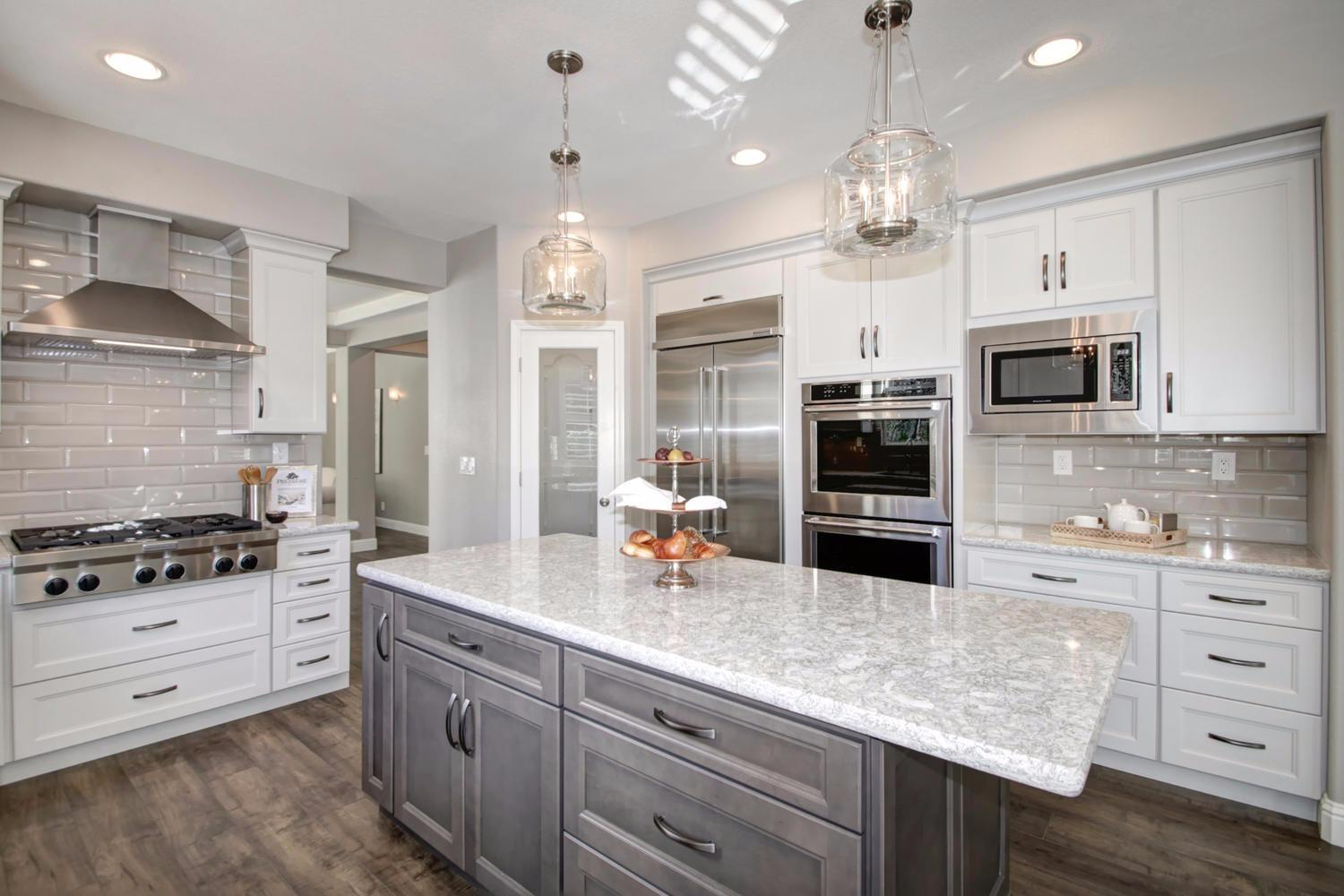 Kitchen island and range, grey and white cabinets and white counters