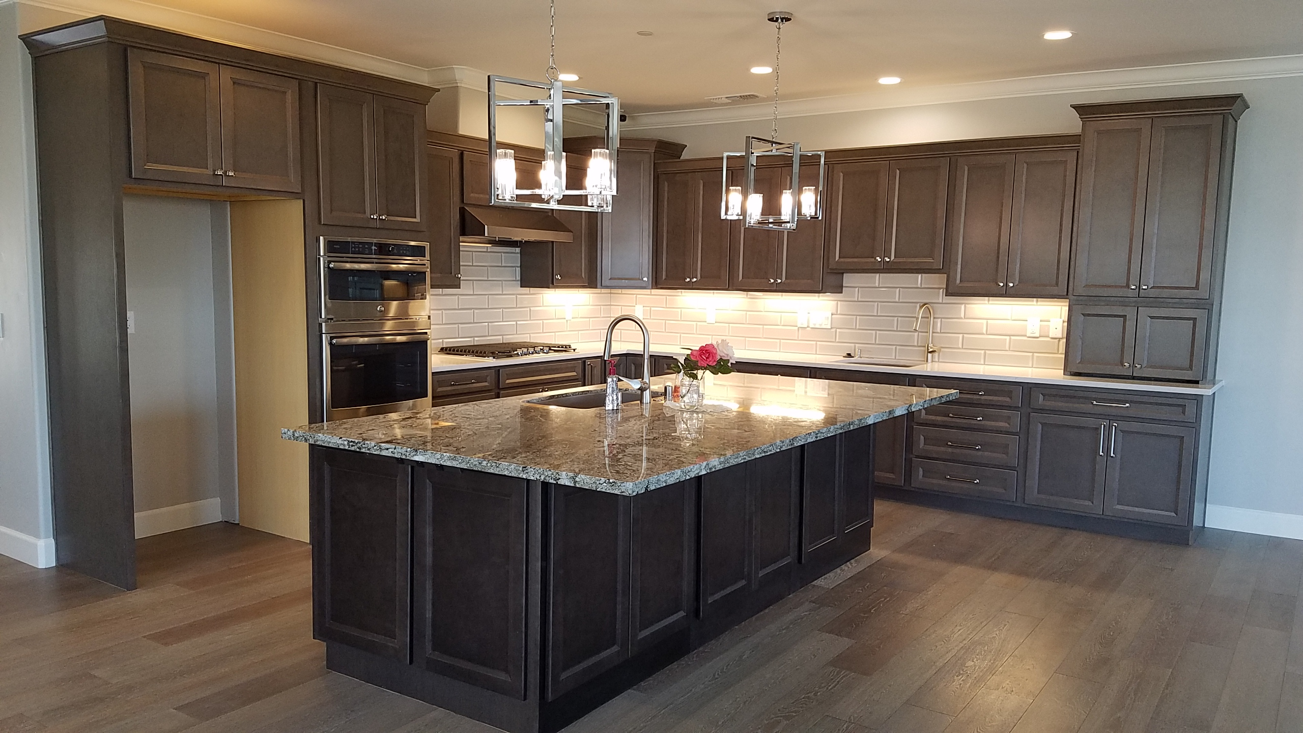 Kitchen island, dark grey cabinets and grey/white counters