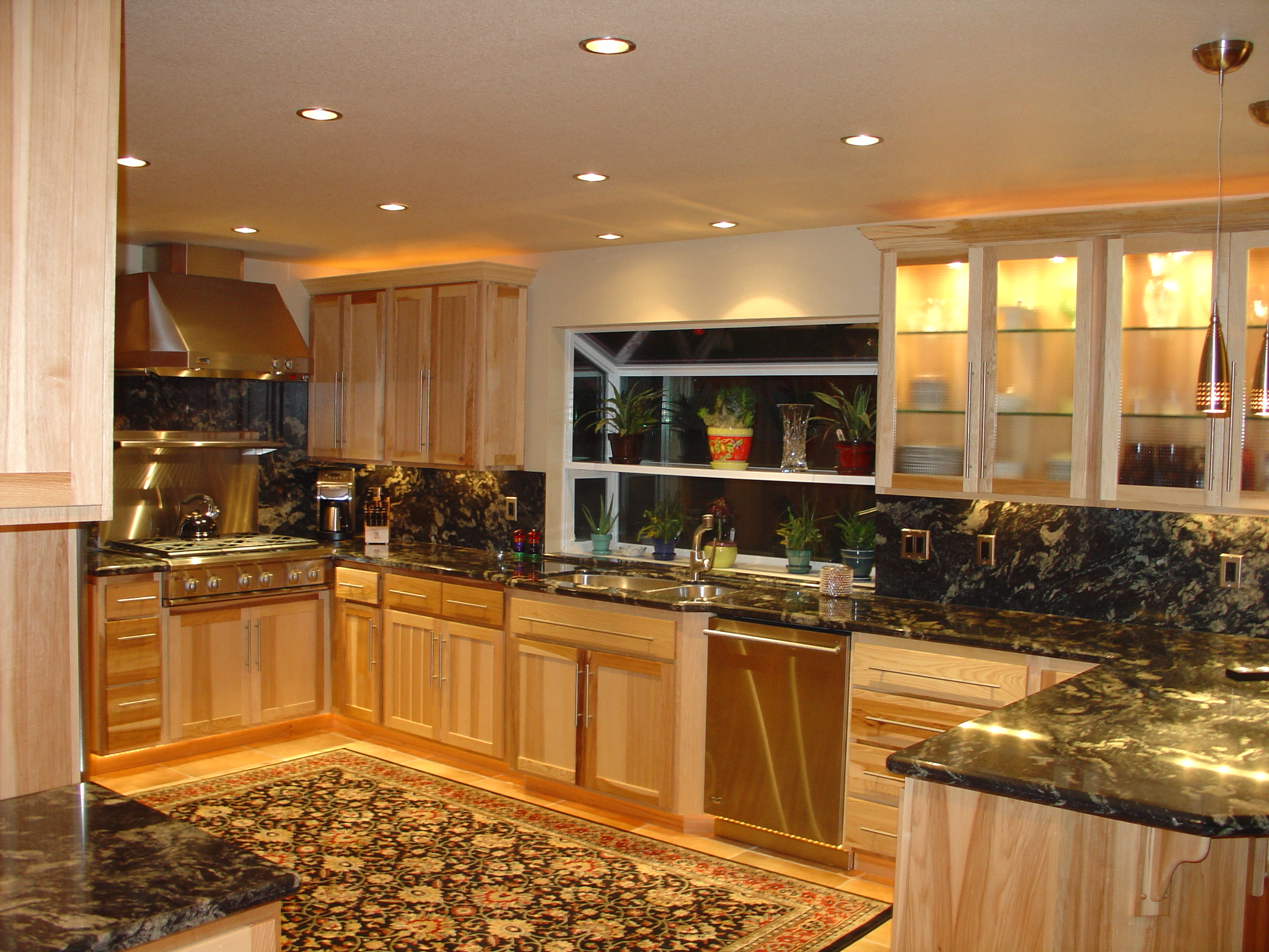 Kitchen with range and sink, dark counters and light sanded cabinets