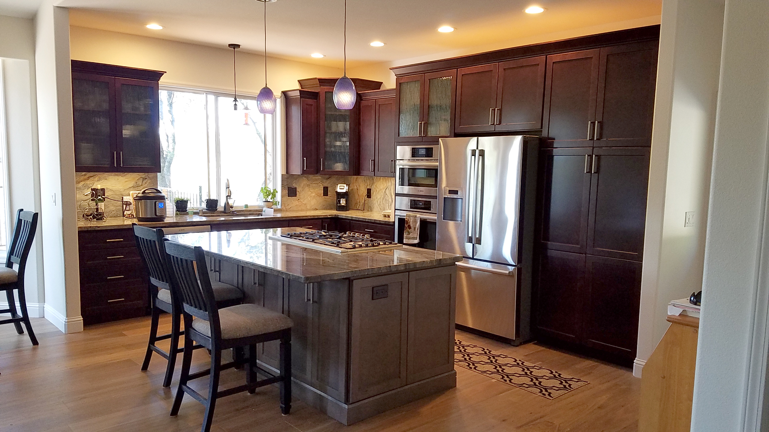 Grey kitchen island, light grey counters and cherry cabinets