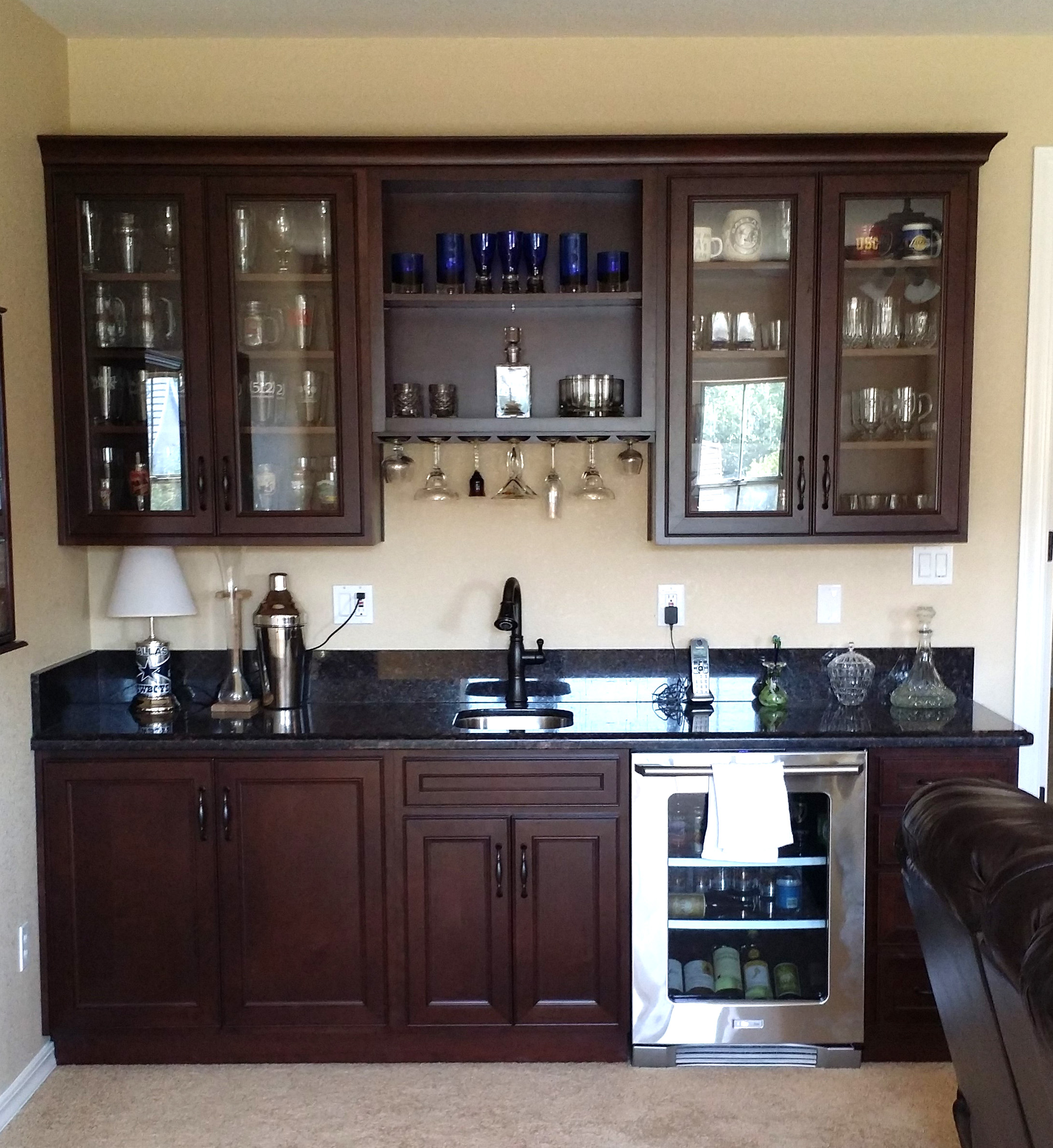 Wet bar with dark cherry cabinets and a black counter top.