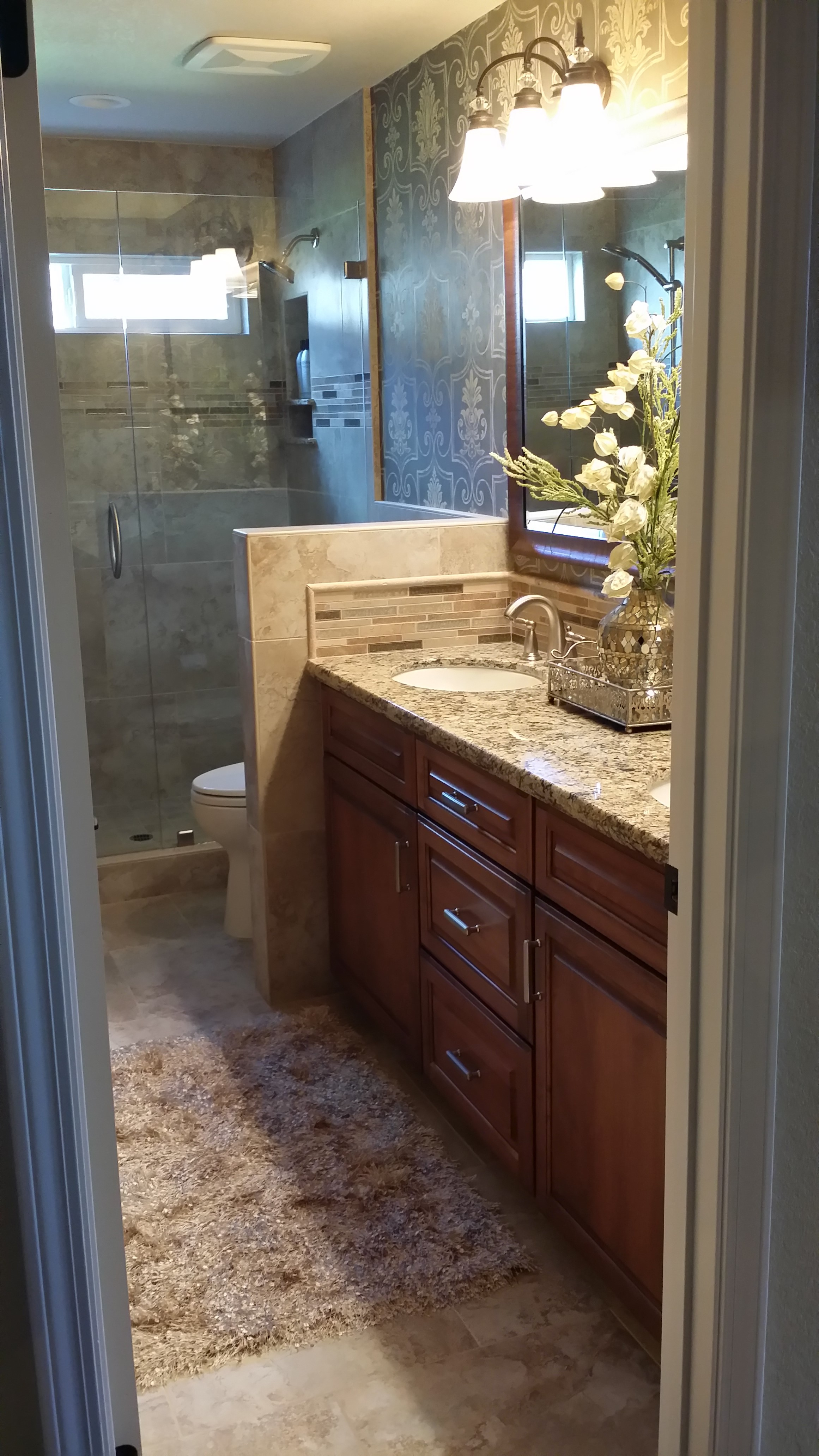 Bathroom vanity with cherry cabinets and granite counter, shower and toilet in the background.