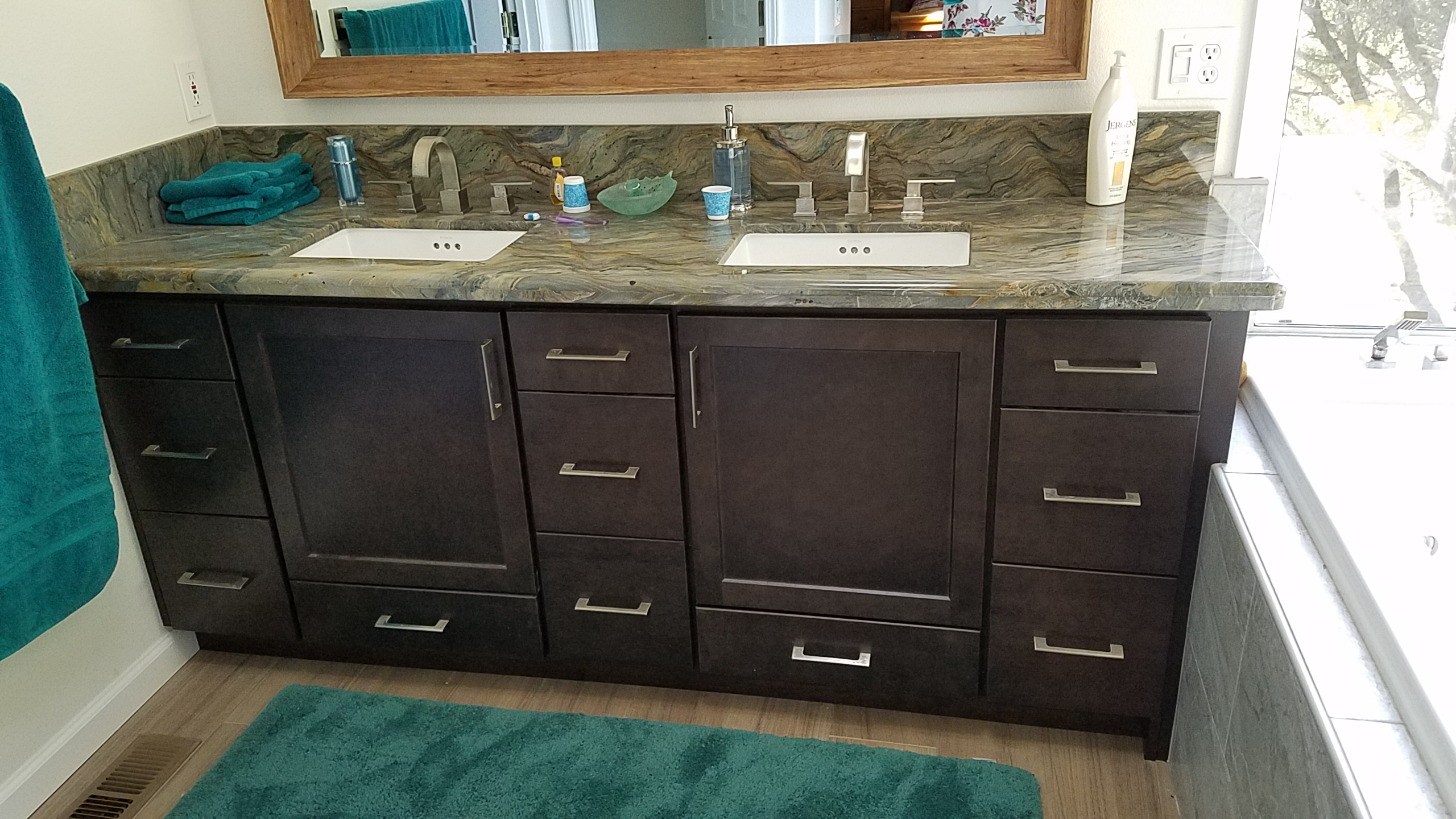 Bathroom vanity with dark cherry cabinets and tan marble counter.