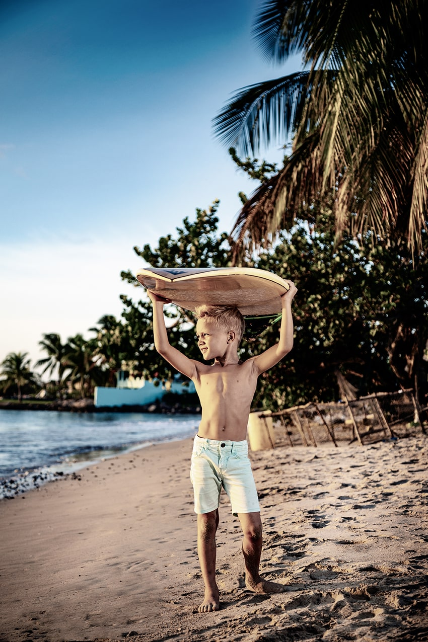 kid with surfboard on the beach