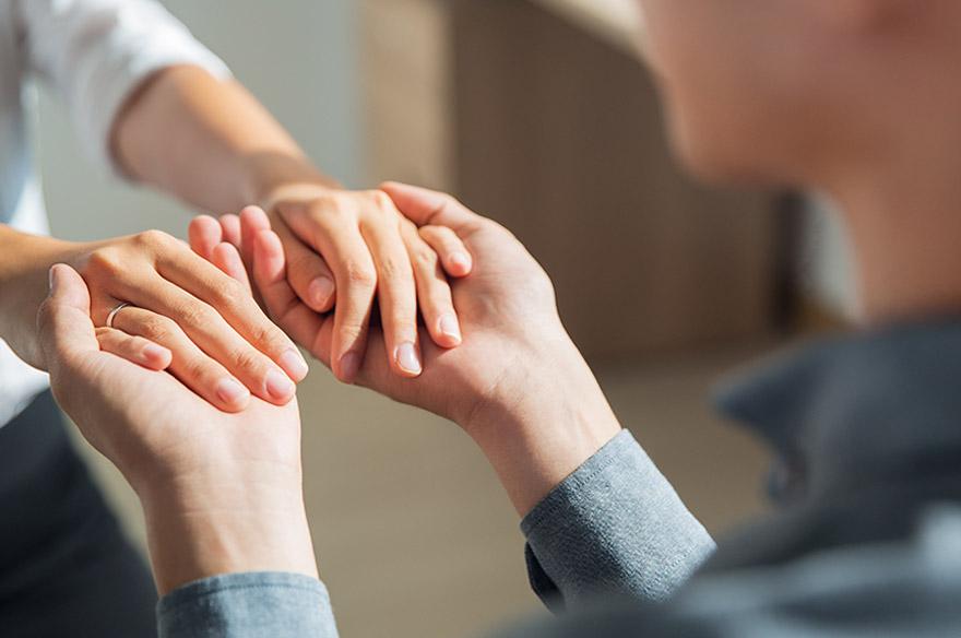 Una persona sujetándole las manos a otra