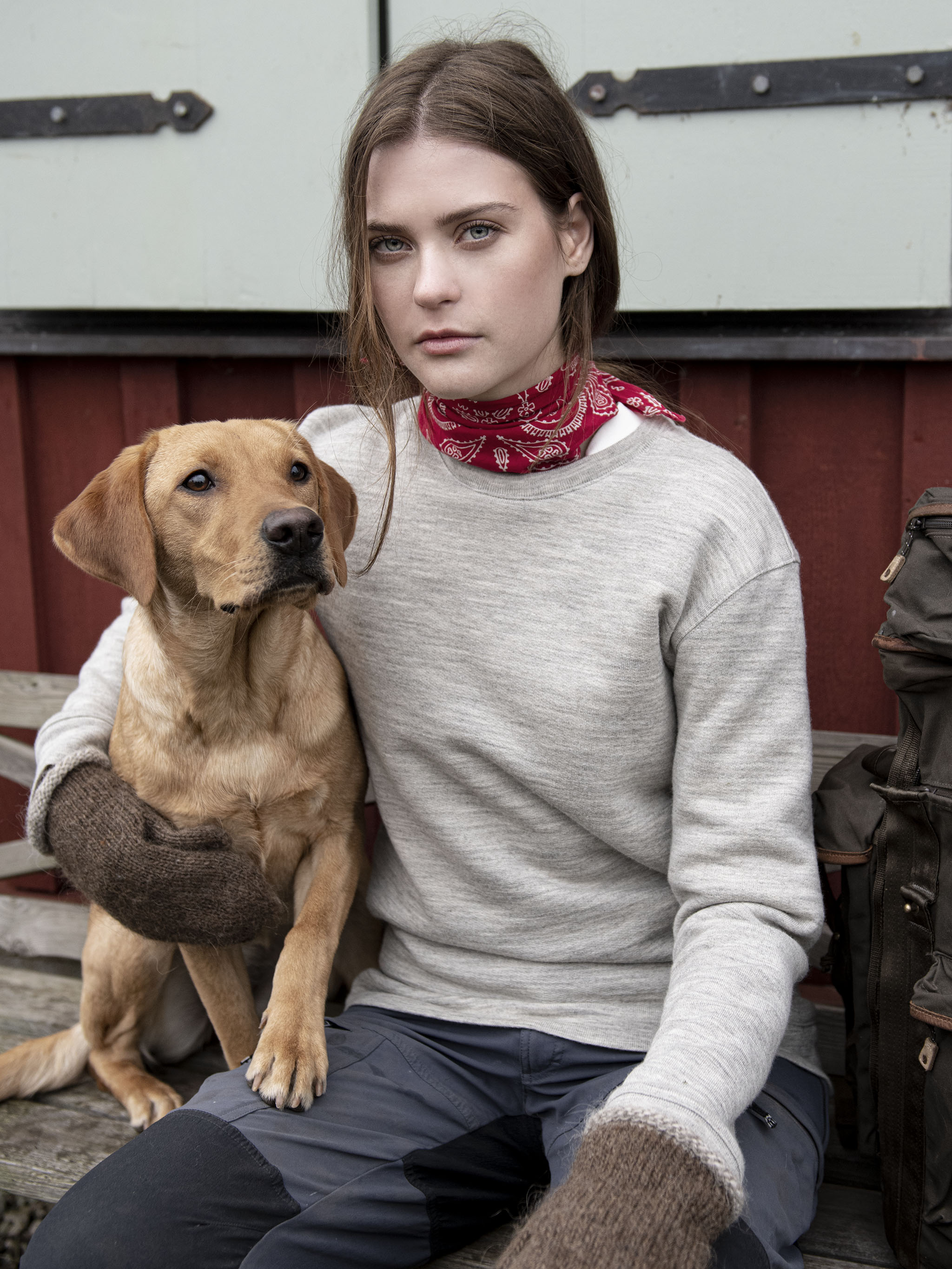 A white Swedish woman with brown hair wearing a woollen grey sweatshirt holding a golden coloured hunting dog, sitting in front of a typical red-painted Swedish house