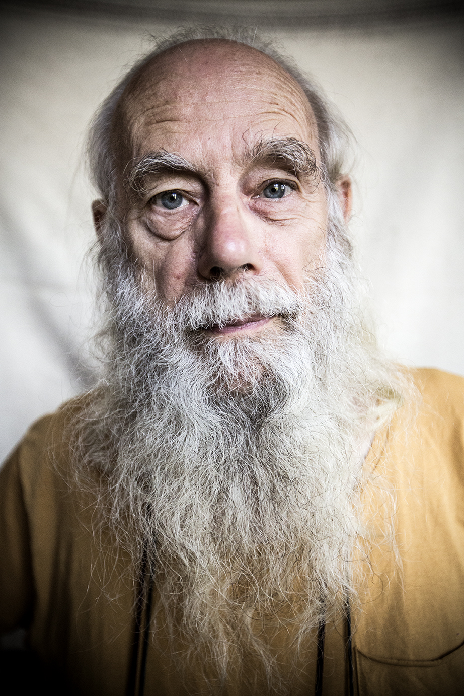 A man in his sixties with white hair and a long beard stares intently into the calendar.
