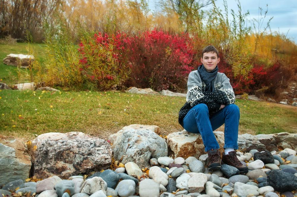 Boy sitting on rocks in sweater