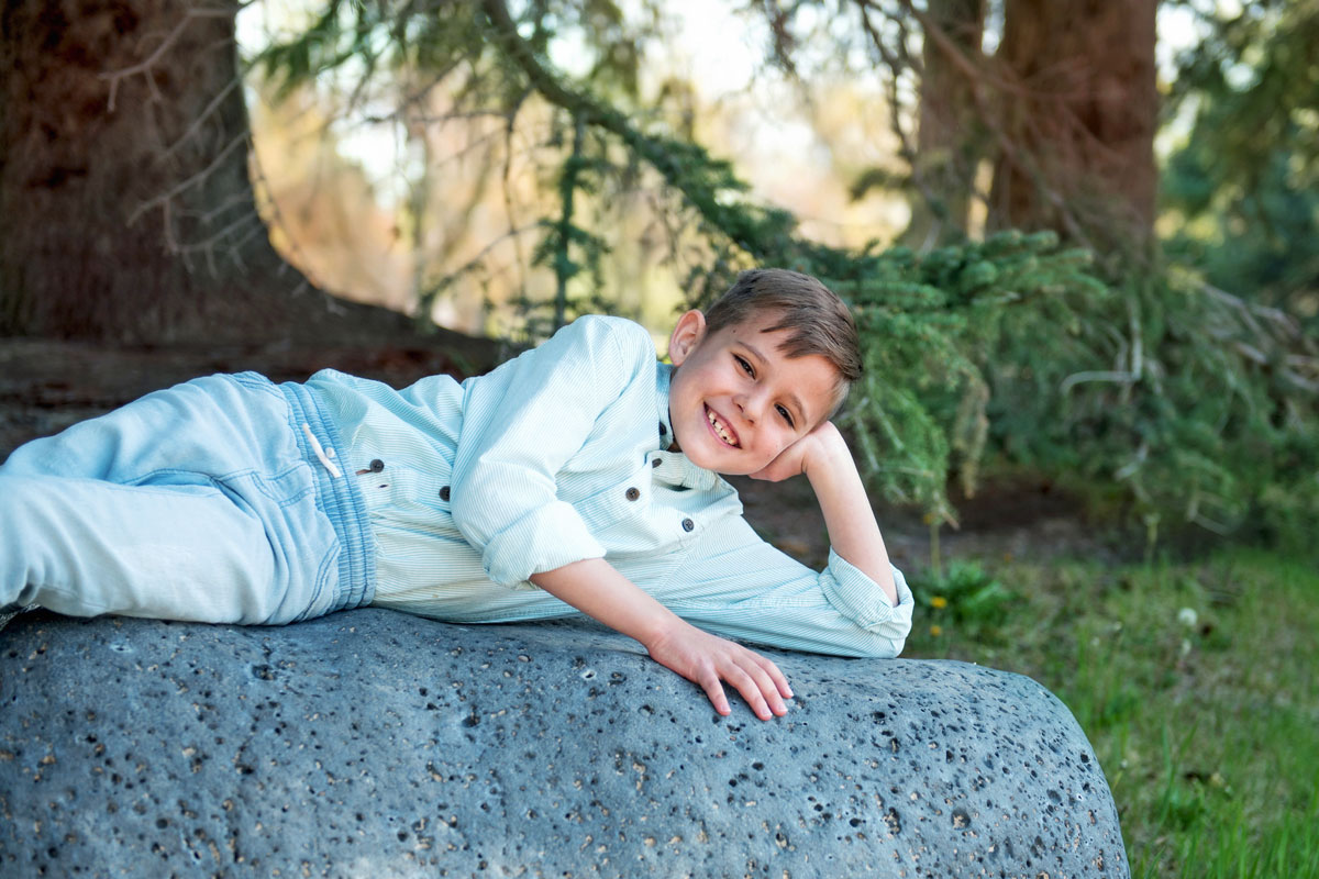 Boy sitting on rocks in sweater