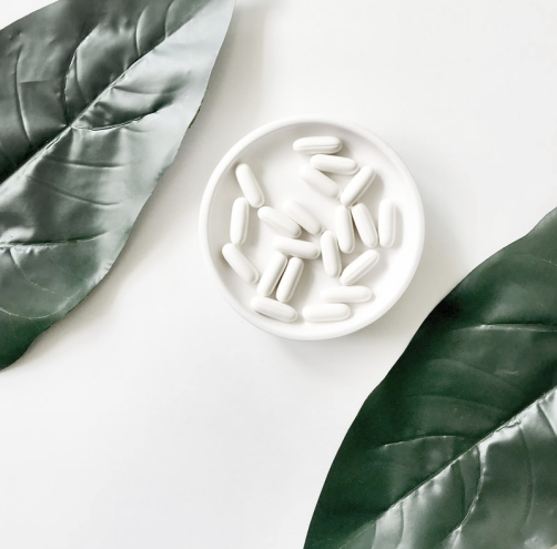 Drug plan optimization for your workforce, image showing pills in a bowl next to two leaves