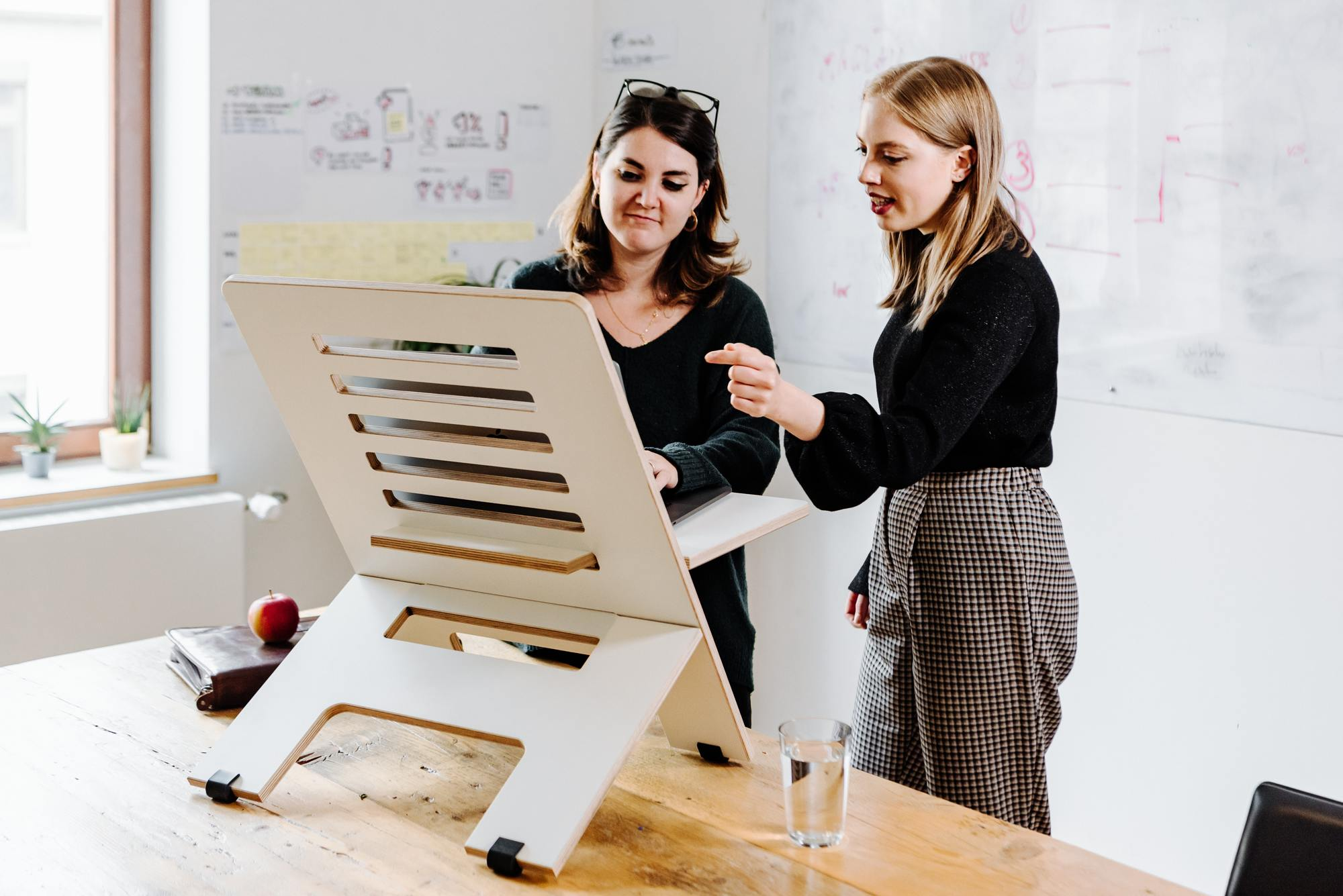 Two women in an office standing in front of a laptop on a desk stand.