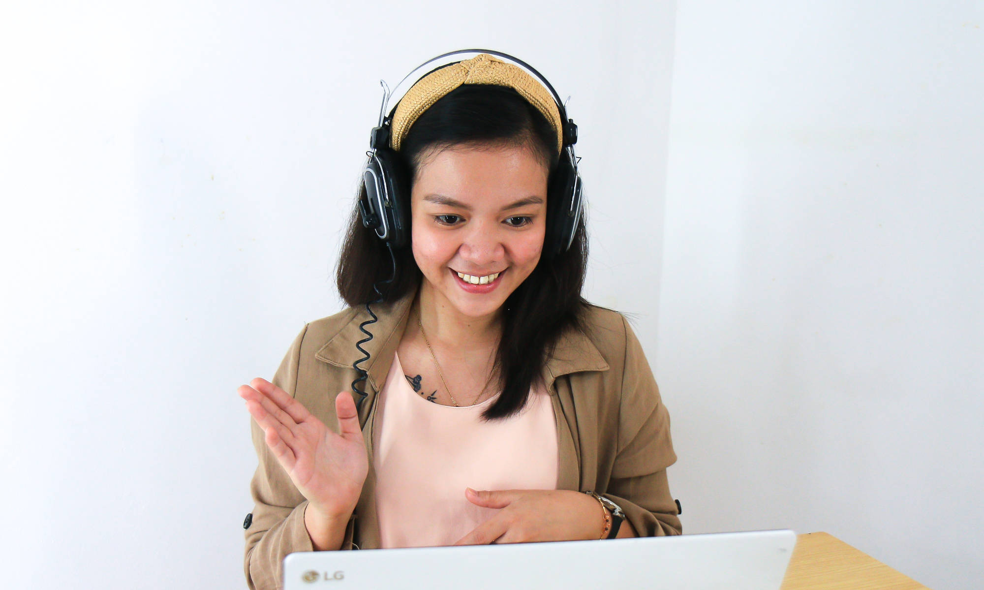 Young asian woman smiling in front of her laptop, with her hands indicating she's learning directions.