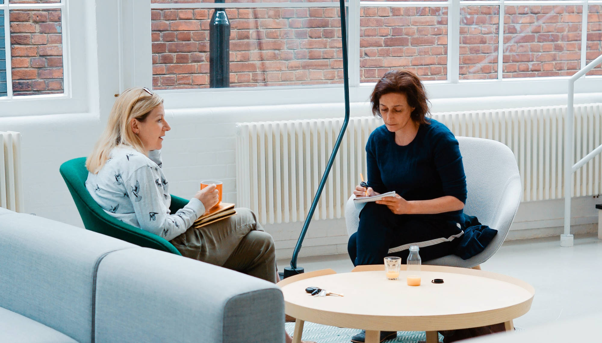 Two women sitting on couches in an office having a serious discussion.