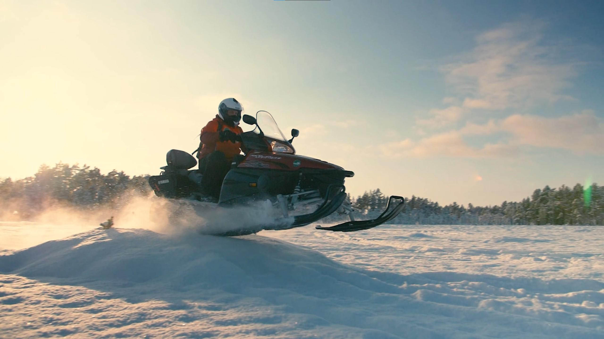 Snowmobile doing a jump in winterlandscape
