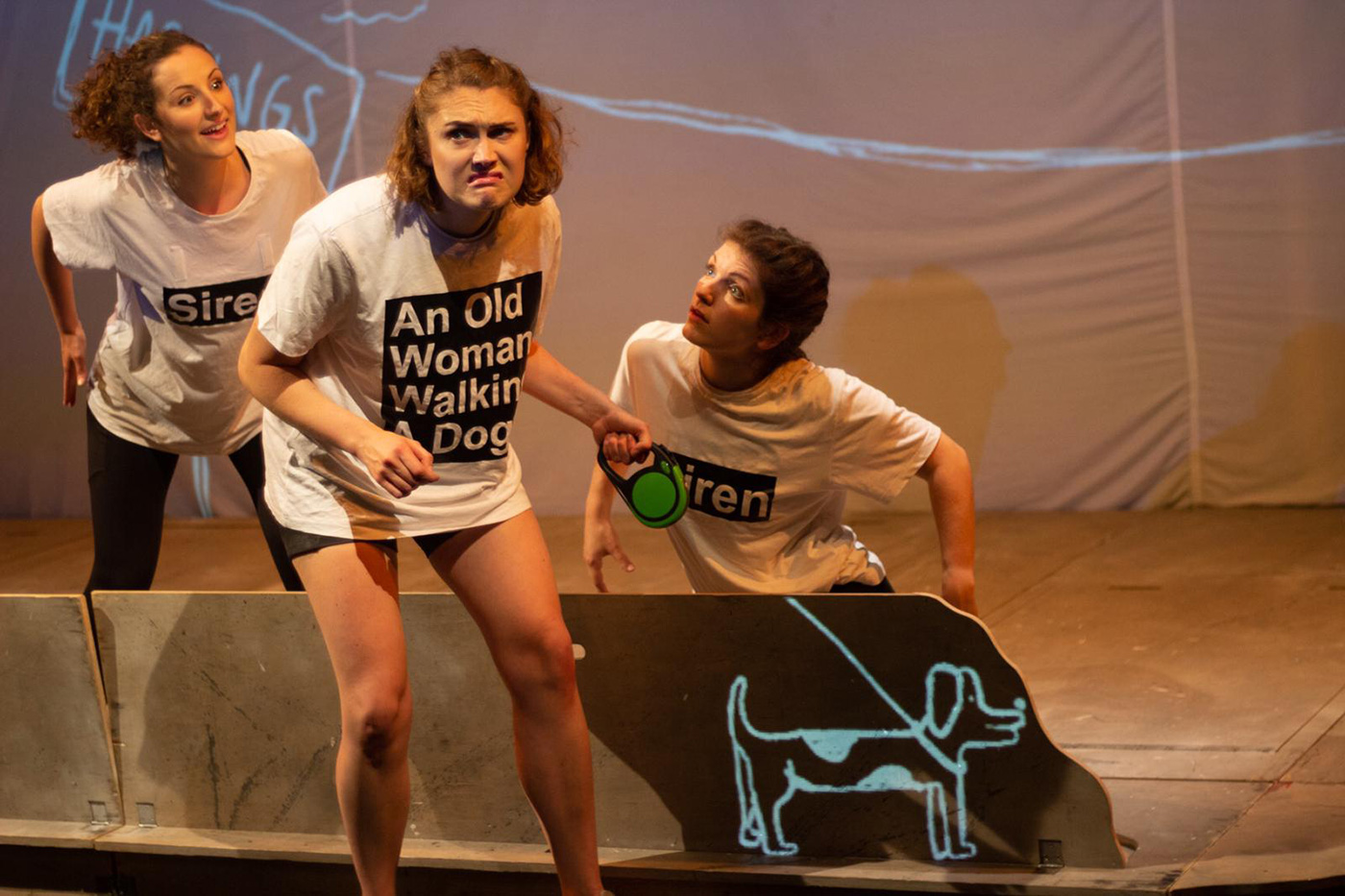 three female actors performing with dog prop