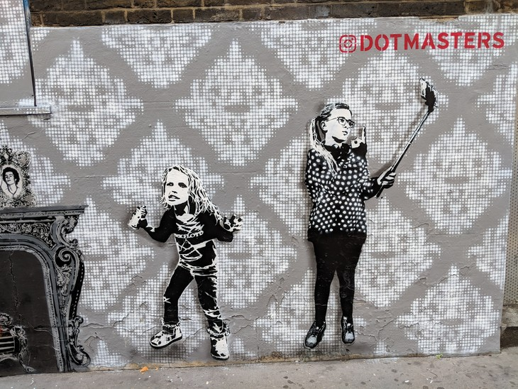 street art featuring two young girls with a Dotmasters tag