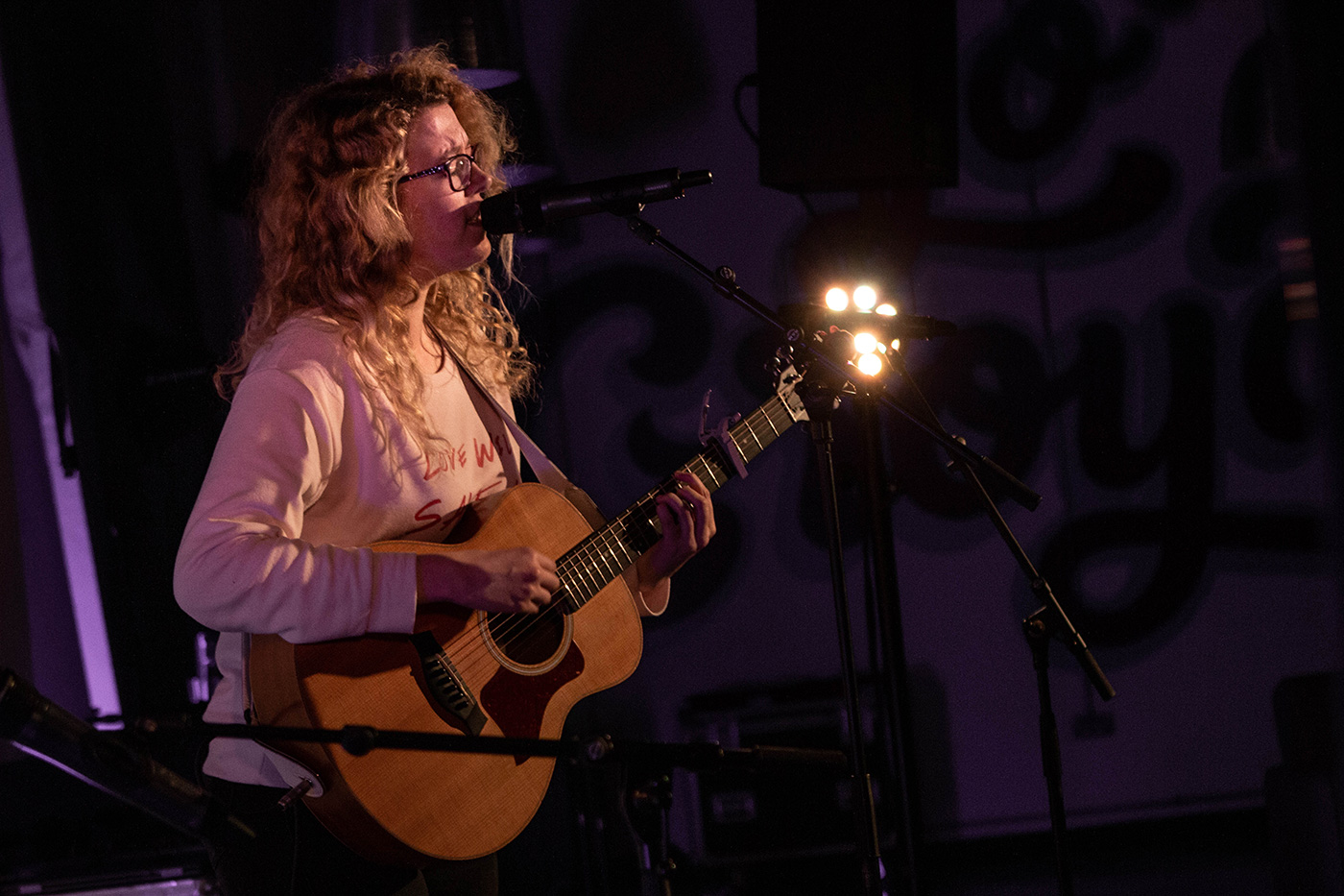 A female solo musician singing and playing the acoustic guitar