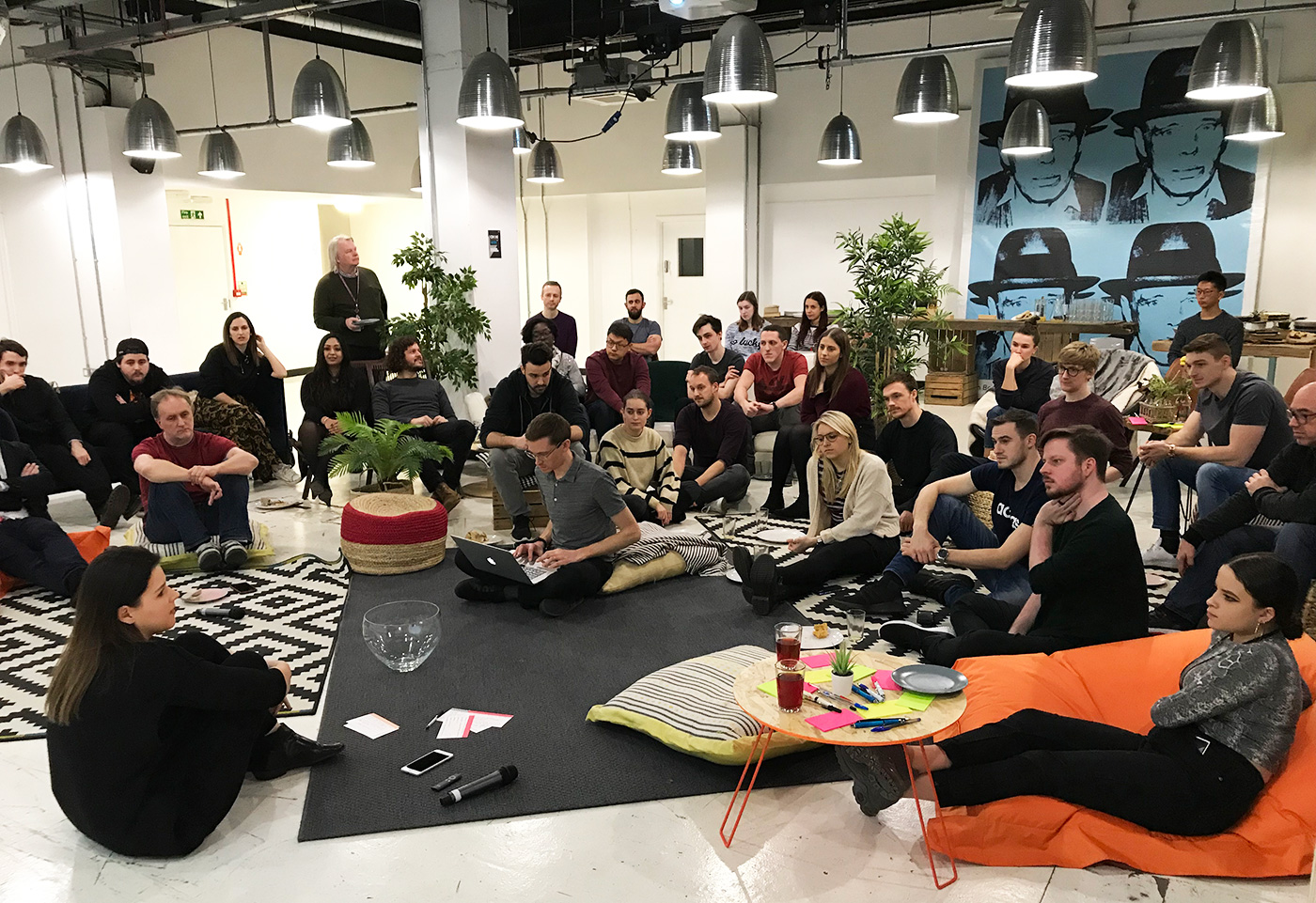 large, relaxed group meeting with people sitting on floor