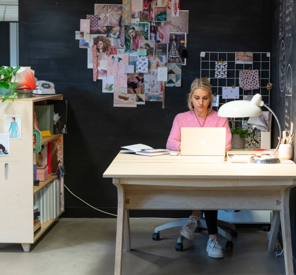 girl working at desk with moodboard