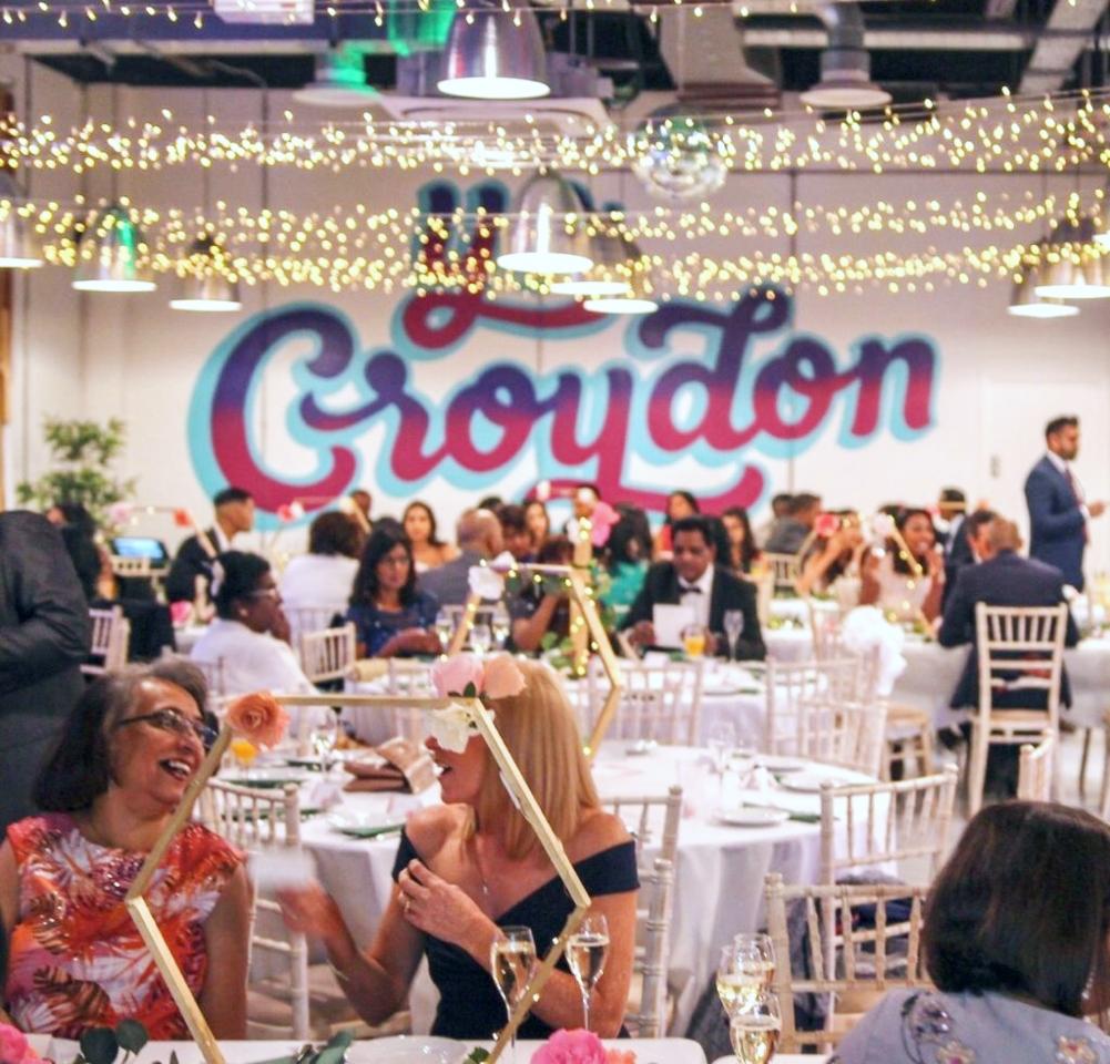 Wedding scene in event space with Yo Croydon mural