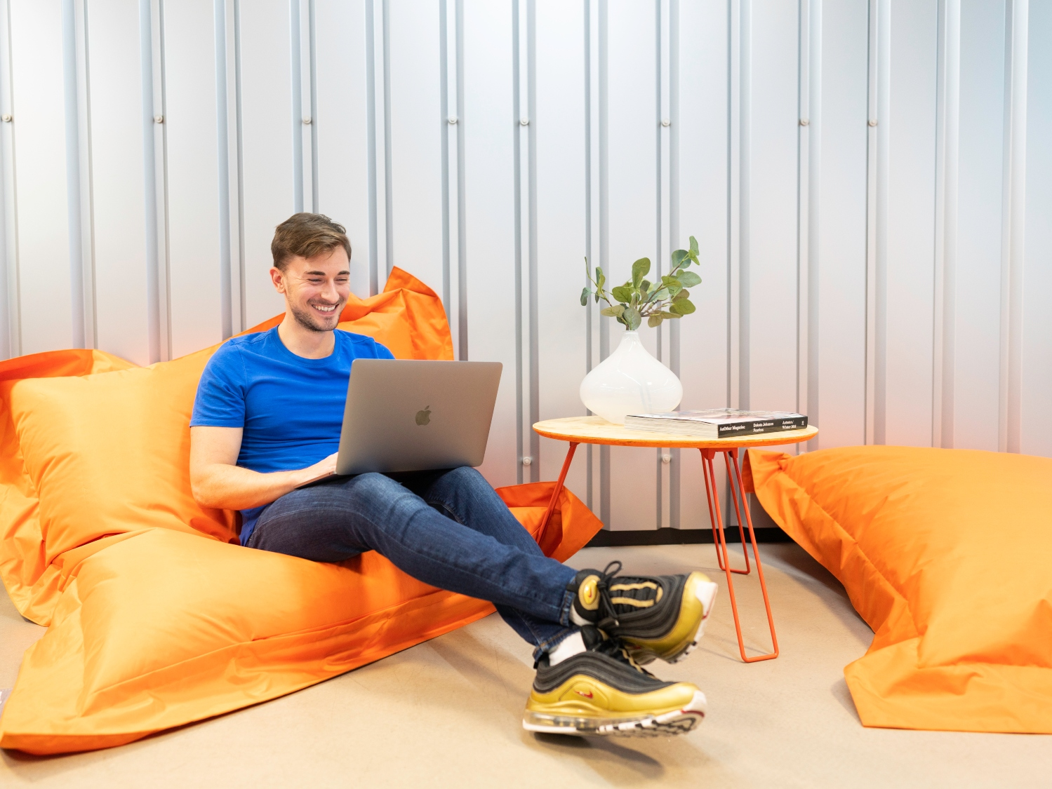 man using laptop on bean bag smiling