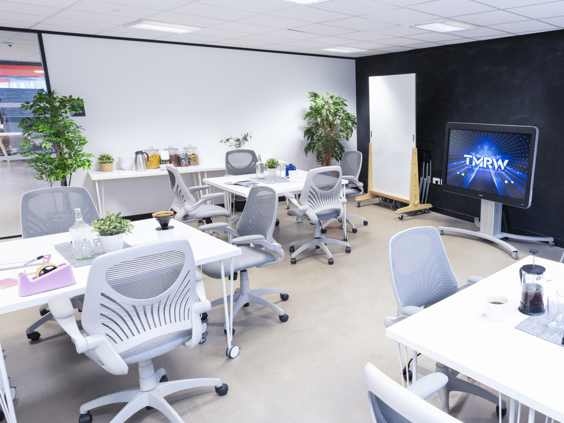 Meeting room with multiple tables and monitor
