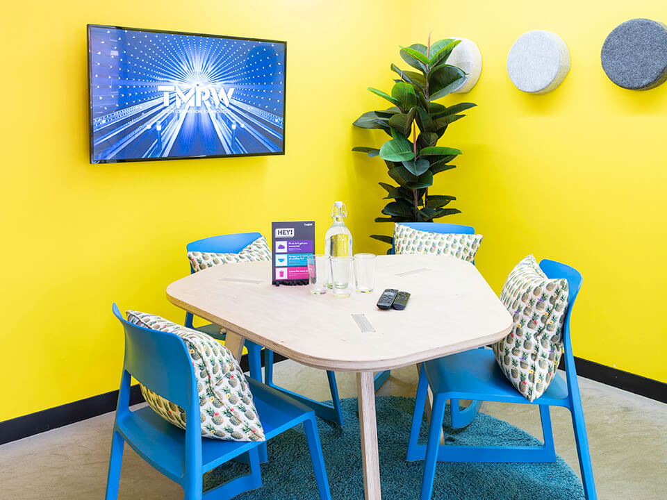bright yellow meeting room with screen and 4 seats