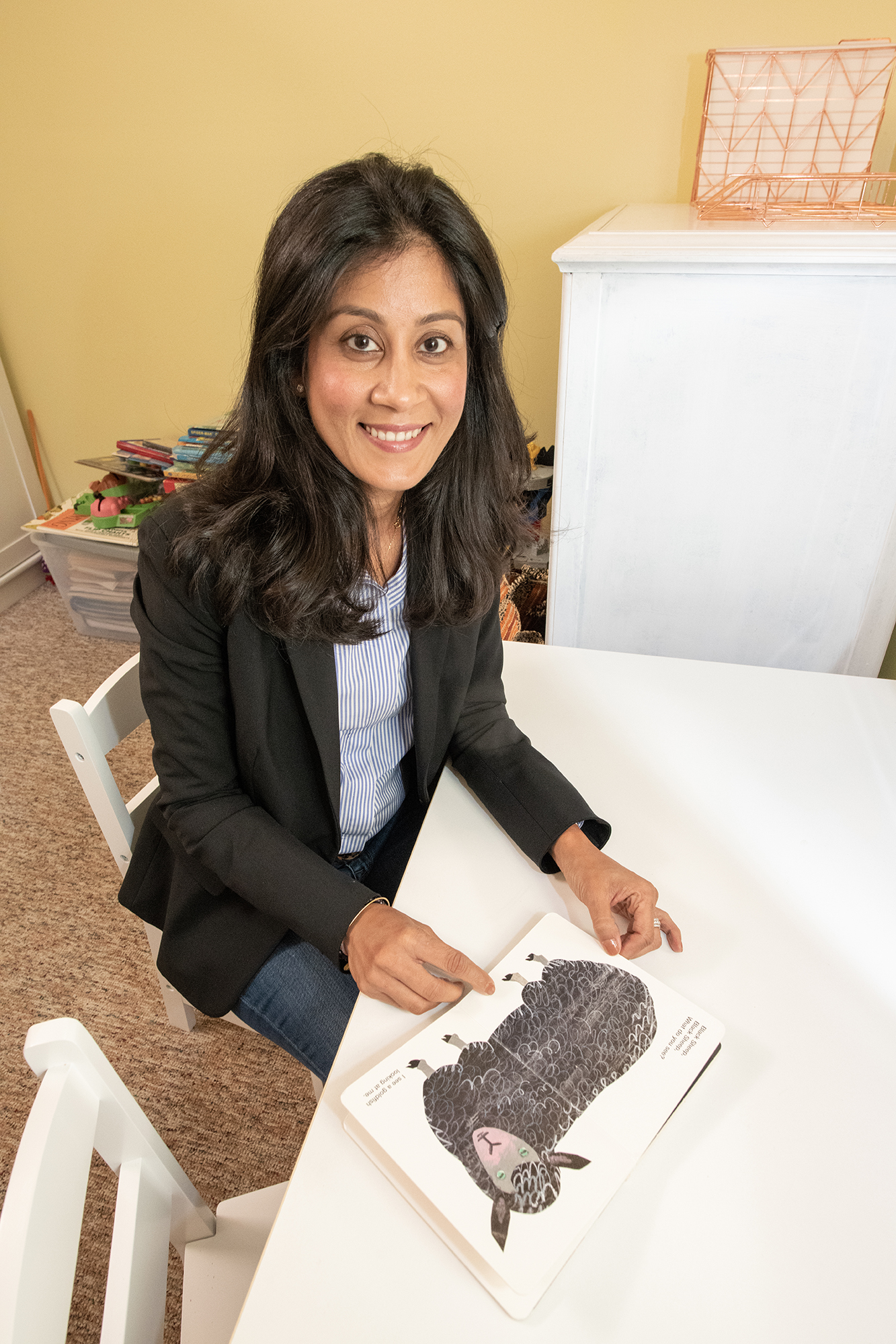 Purvi Gandhi sitting at a table with a picture of a lamb