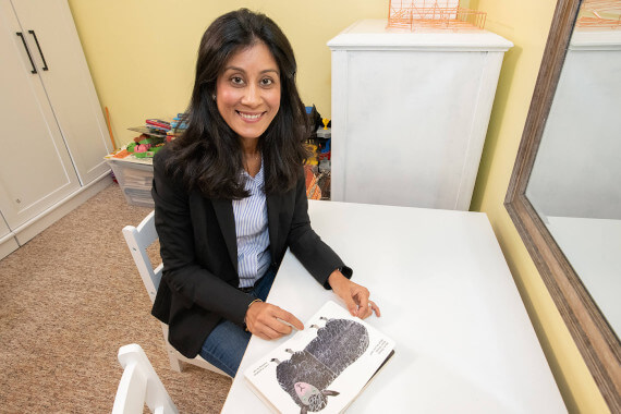 Purvi sitting at a table with a picture of a lamb