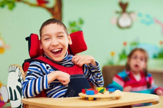 smiling child in wheelchair playing a game