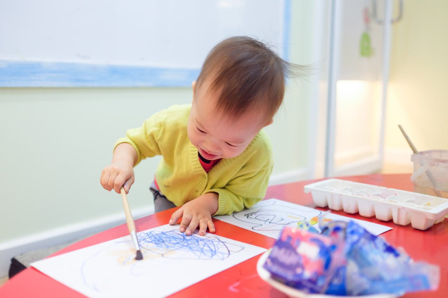 cute smiling 1-year-old 18-month toddler baby boy child painting with brush and water colors at art therapy