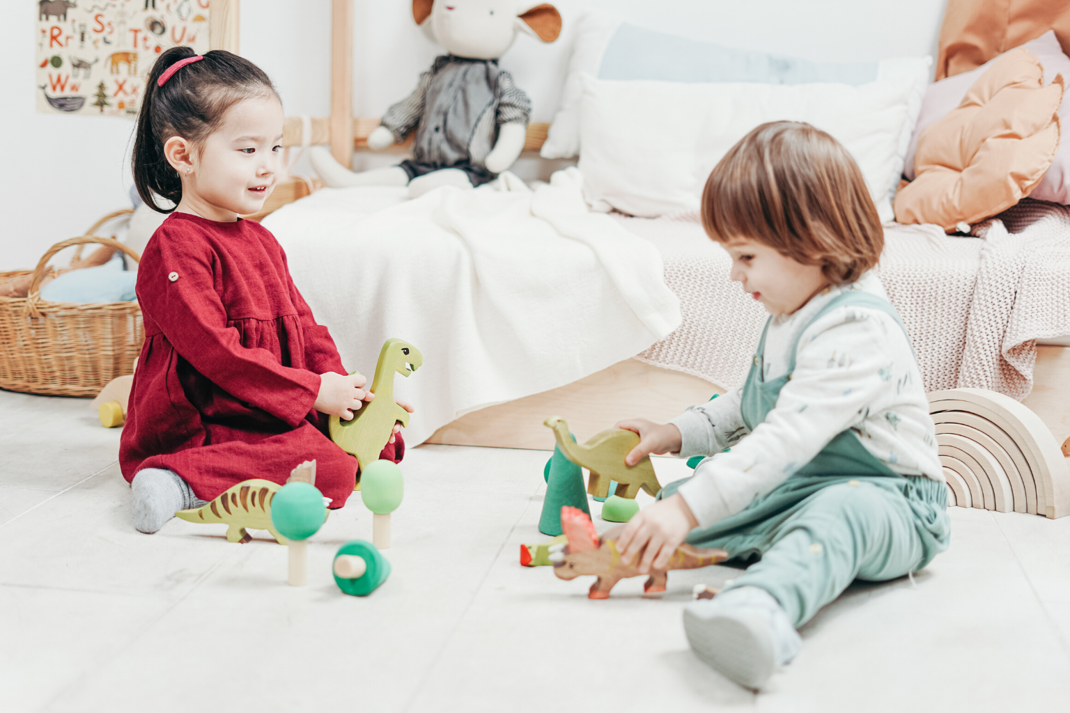 two children toddlers sitting down playing with toys