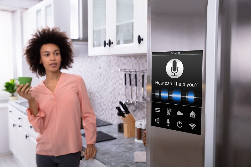 người phụ nữ nói chuyện với trợ lý ảo được tích hợp trong tủ lạnh nhà bếp