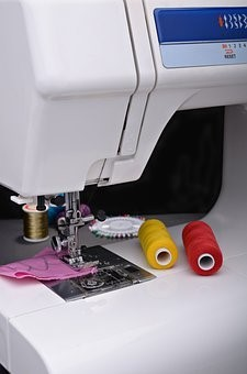 A white sewing machine and multi-colored threads for stitching fabric