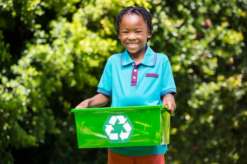 A boy in children's wear holding a recycling box