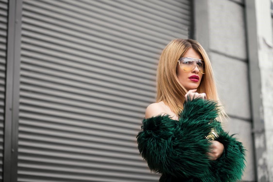 A fashionista in women's wear wearing a green fur jacket with sunglasses