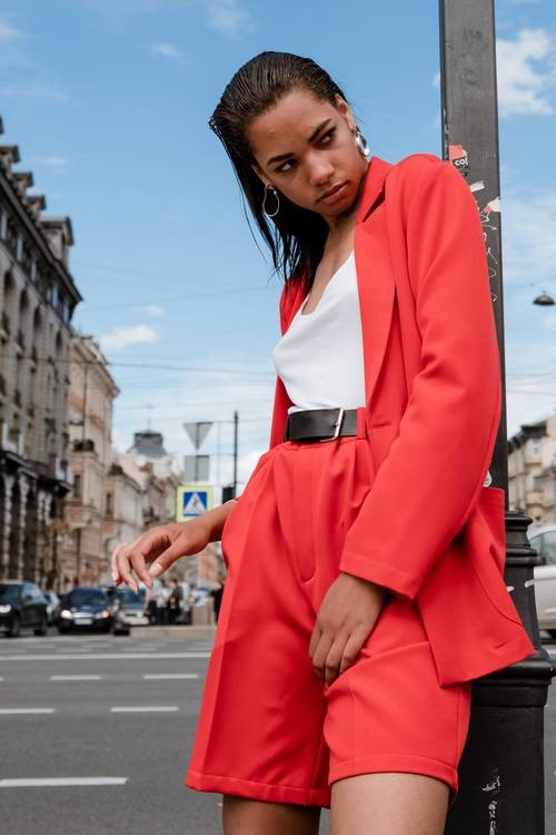 A girl in a red blazer leaning against a lamp post.