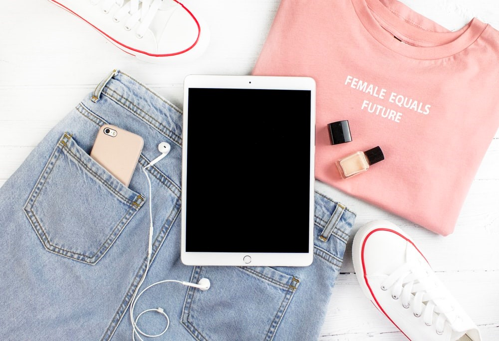 A pair of blue jeans with a pink top and white sneakers