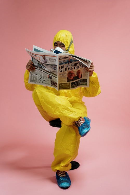 A Man Wearing PPE, Reading A Newspaper