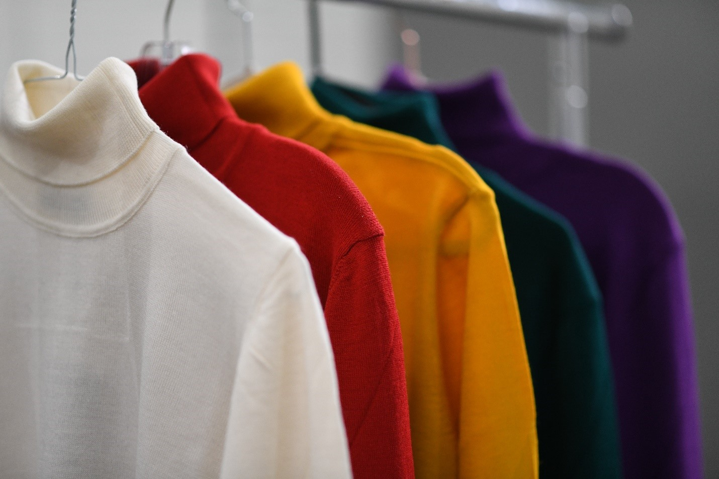 Assorted turtleneck apparel hanging in a clothing company