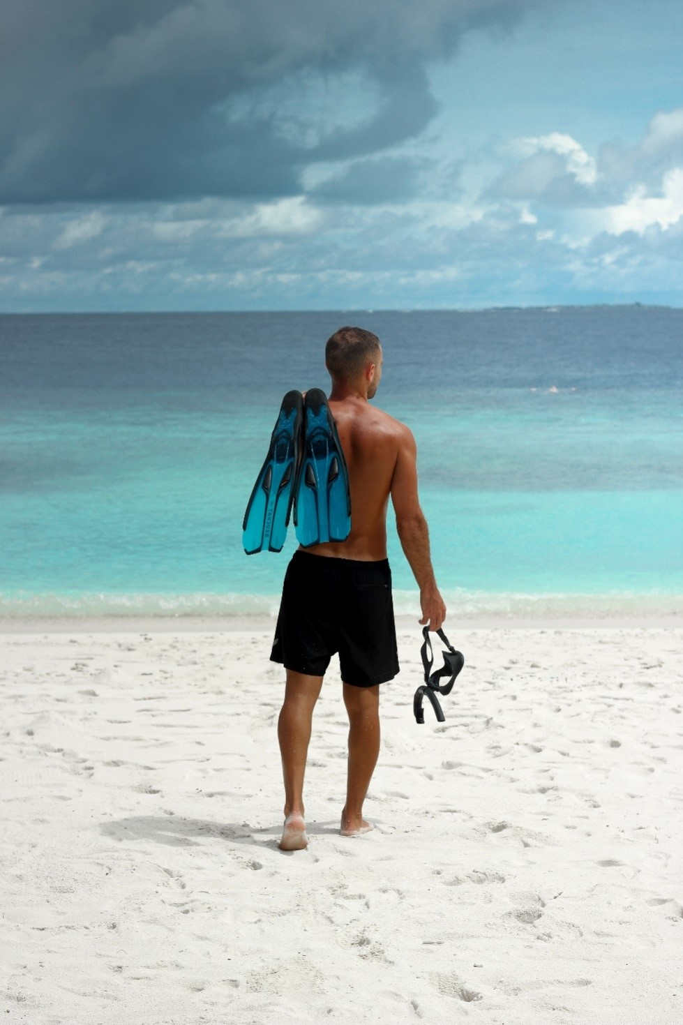 A person wearing black apparel shorts on the beach