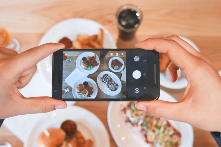 Person taking a picture of his meal with a smartphone
