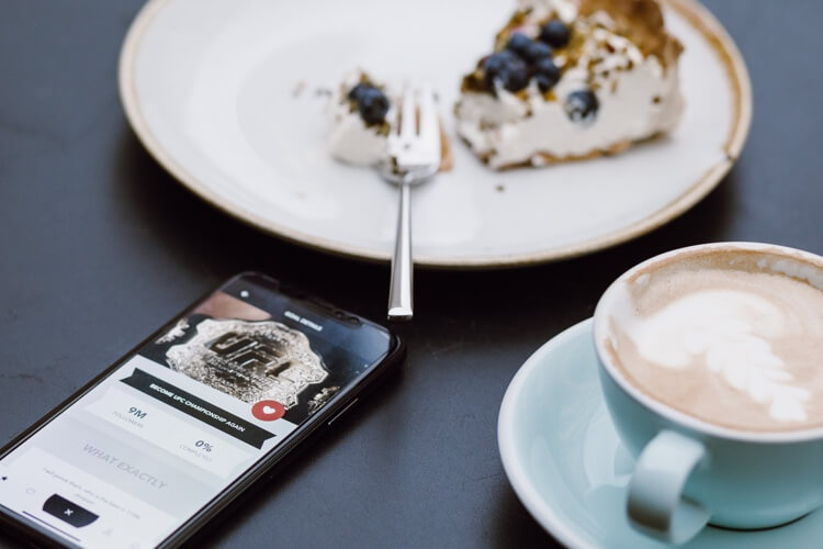 Smartphone on a table between a plate of half-eaten blueberry pie and cappuccino