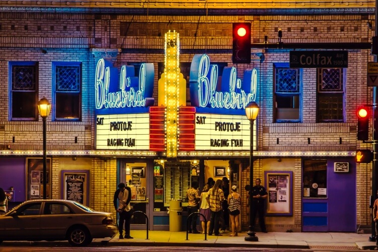 People standing in front of a jazz theater with a large, neon marquee.