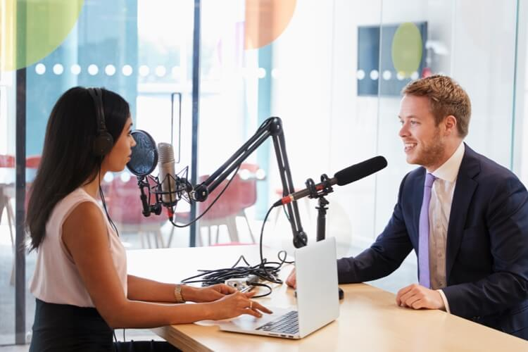 Woman interviewing a man sitting across from her in a podcast studio