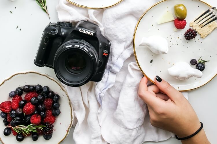 A woman eating dessert with an SLR camera on the table